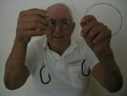 photo of Frank Mundus displaying a couple of environmentally friendly shark hooks